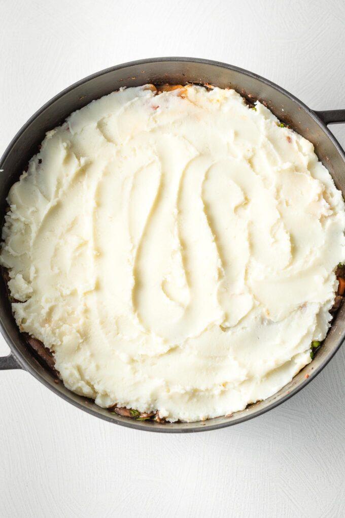 Mashed potatoes spread on top of shepherd's pie.