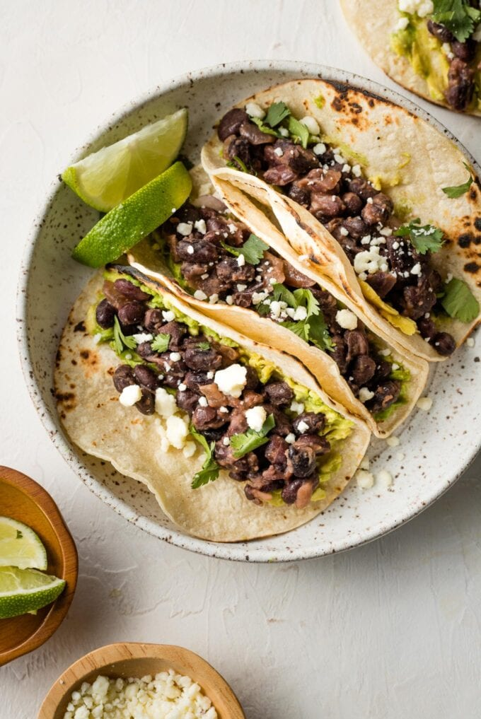 Small bowl with black bean tacos ready to top.