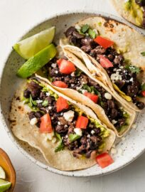 Plate with three black bean tacos.