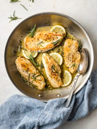 Skillet ready to serve lemon rosemary chicken with sauce.