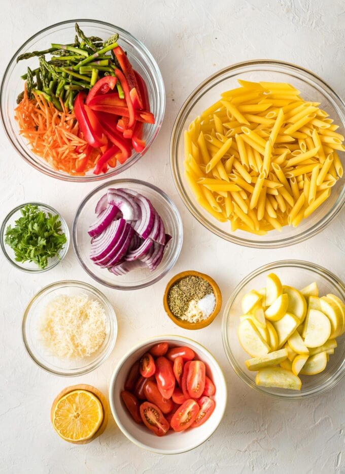 Prep bowls containing dried penne, carrots, asparagus, red bell pepper, yellow squash, red onion, lemon, garlic, and herbs.