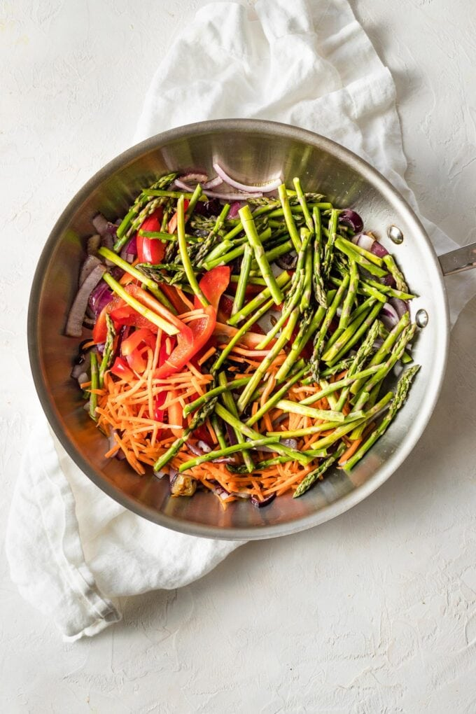 Skillet with asparagus, bell pepper, carrots, and red onion ready to cook.