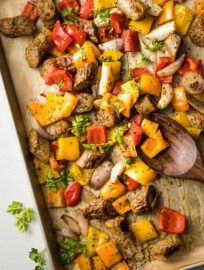 Large sheet pan filled with roasted chicken sausage, peppers, and shallots.