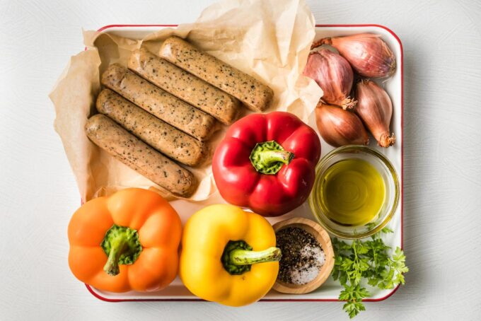 Tray with Italian-flavored chicken sausage links, three whole bell peppers, several whole shallots, herbs, olive oil, salt, pepper, and Italian seasoning.