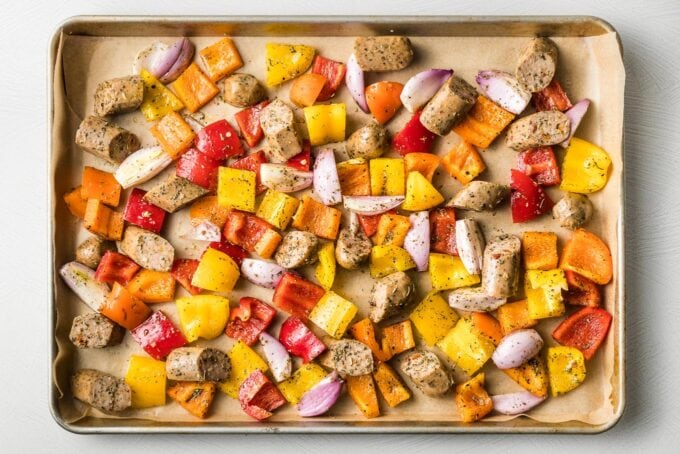 Sausages and veggies, uncooked, spread out on a sheet pan.