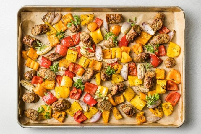Sausages and veggies on the sheet pan after roasting.