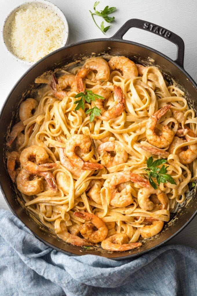 Skillet filled with blackened shrimp Alfredo, mixed together and ready to serve.