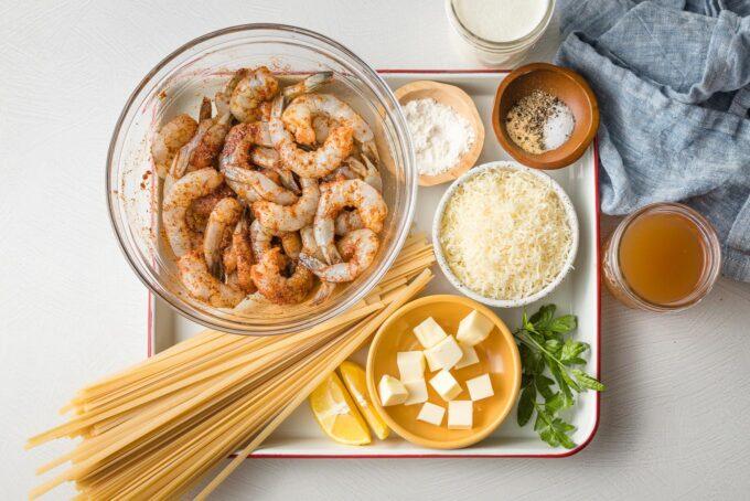 Shrimp with blackening seasoning, fettuccine, butter, Parmesan, flour, cream, broth, parsley, lemon, and seasonings arranged on a tray.