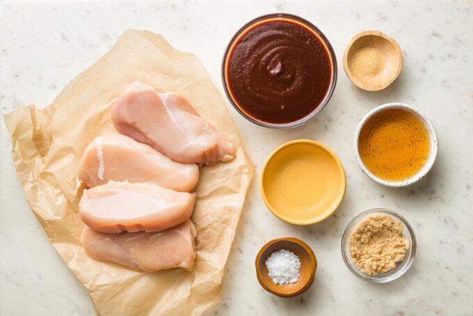 Chicken breasts, BBQ sauce, sea salt, garlic powder, apple cider vinegar, brown sugar, and a bit of water in prep bowls.