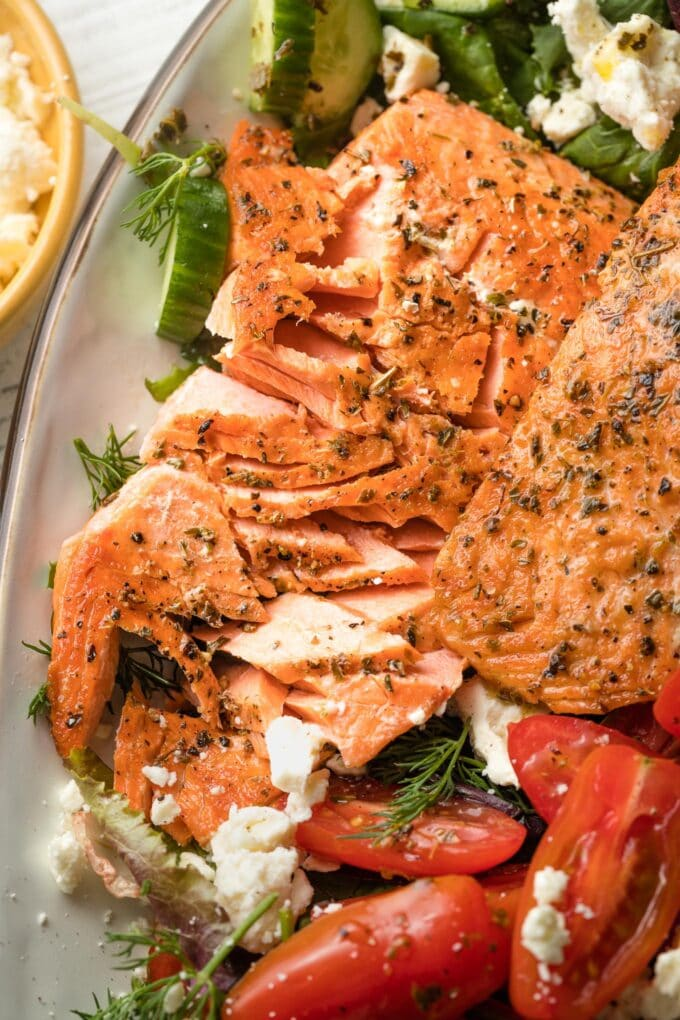 Close-up of flaked salmon filets, with pieces broken off.