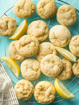 Wire rack piled high with soft lemon sugar cookies on a blue background.