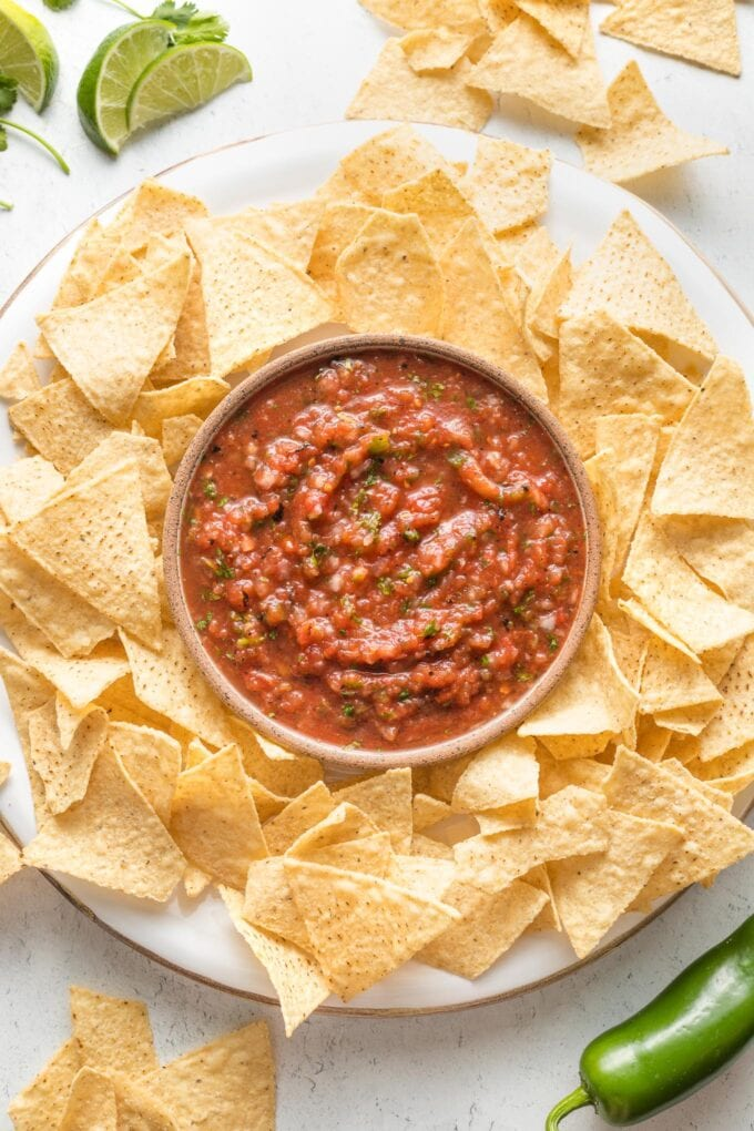 Bowl of blender salsa on a tray surrounded by tortilla chips.