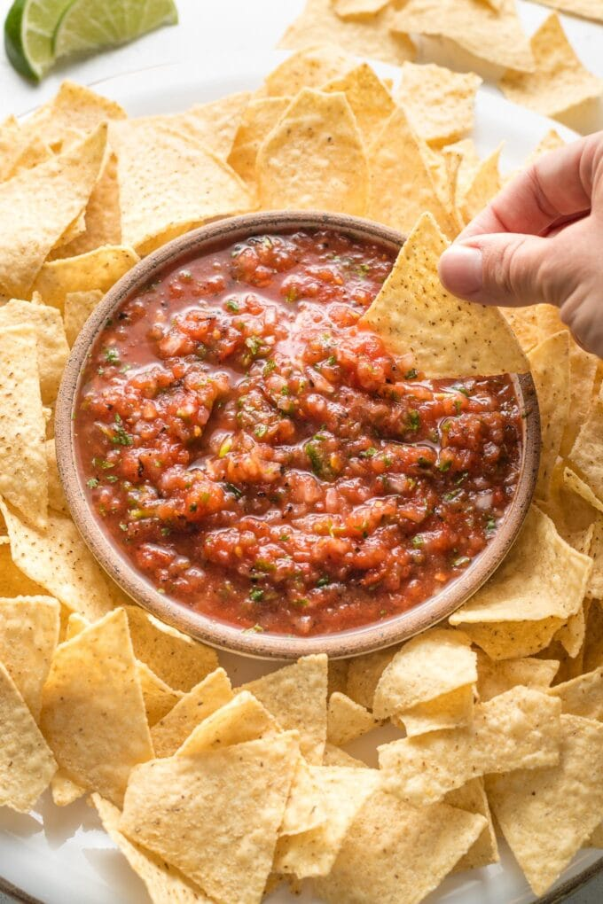 A chip being dipped into a bowl of restaurant-style blender salsa, surrounded by chips.