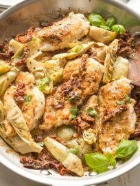 Skillet with cooked chicken breasts, sun-dried tomatoes, and artichokes in a light cream sauce, garnished with basil.