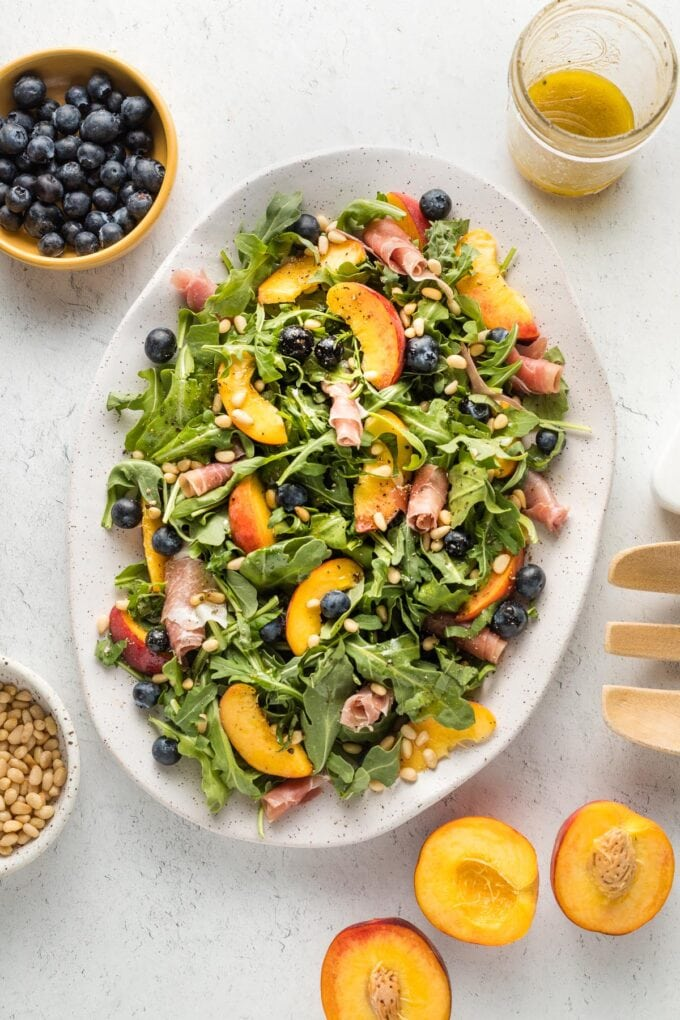 White platter with a peach arugula salad, with prosciutto, blueberries, pine nuts, and a white wine vinaigrette, ready to serve.