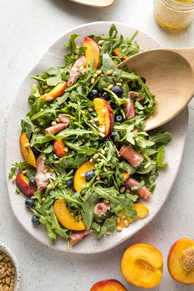 White platter with peach arugula salad and salad tongs preparing to serve portions.
