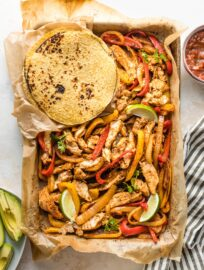 Sheet pan filled with fajita-seasoned chicken and veggies, surrounded by tortillas and small bowls of avocado and salsa.