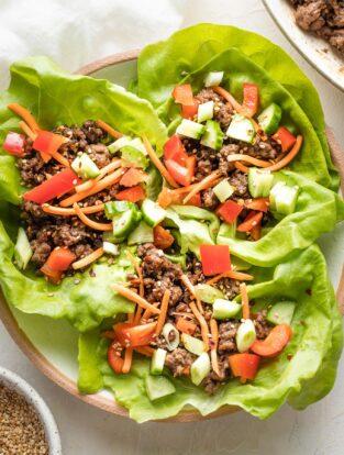Three Korean beef lettuce wraps piled into a white bowl, ready to eat.