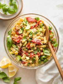 Clear serving bowl holding a pasta salad with chickpeas, roasted red peppers, cucumbers, and herbs.