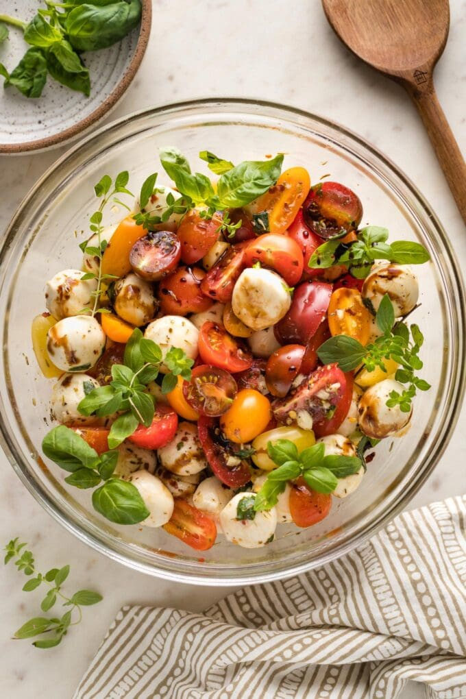 Bowl of marinated mozzarella balls served with cherry tomatoes and herbs as a salad.