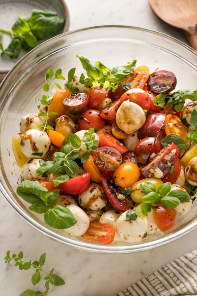 Side view of the bowl of marinated mozzarella with tomatoes.