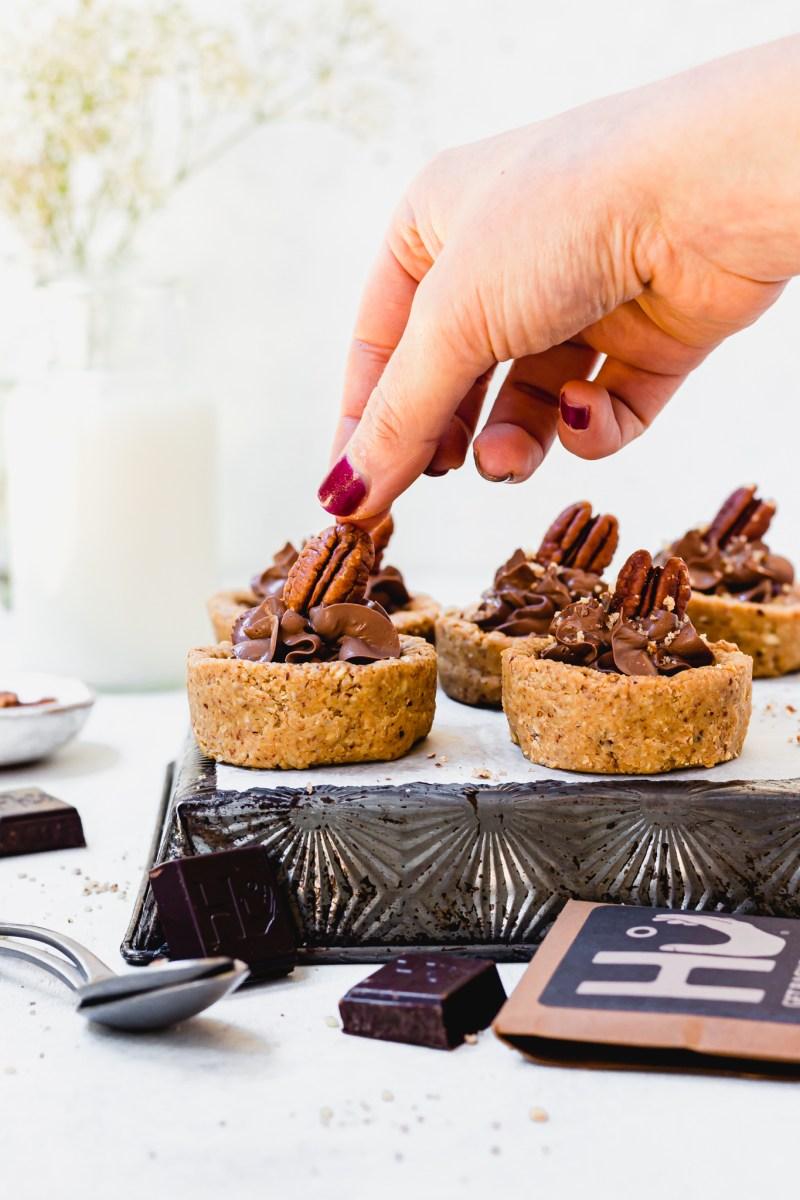 Placing a pecan on a Mini Chocolate Mousse Pecan Tart