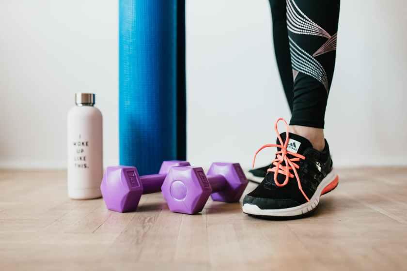 unrecognizable female athlete standing near sport accessories