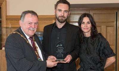 Derry City and Strabane District Council Mayor, Councillor Maolíosa McHugh pictured presenting Derry Singer Songwriter Johnny McDaid with an award in recognition of his achievements in the music industry during a reception in the Guildhall with his fiancé actress Courtney Cox. Picture Martin McKeown. Inpresspics.com.