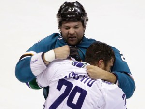 San Jose Sharks' John Scott, top, fights with Vancouver Canucks' Tom Sestito during the first period of an NHL preseason hockey game Tuesday, Sept. 23, 2014, in Stockton, Calif. (AP Photo/Marcio Jose Sanchez)