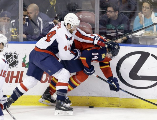 Washington Capitals defenseman Brooks Orpik (44) checks Florida Panthers left wing Tomas Fleischmann (14) during the first quarter of an NHL hockey game, in Sunrise, Fla., Tuesday, Dec. 16, 2014. (AP Photo/Alan Diaz)