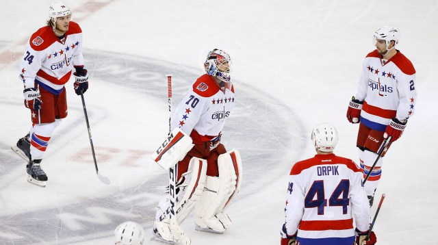 Washington Capitals goalie Braden Holtby (70) skates off the ice with defenseman John Carlson (74), defenseman Brooks Orpik (44) and defenseman Matt Niskanen (2) after the New York Rangers scored in overtime to win Game 5 in the second round of the NHL Stanley Cup hockey playoffs, Friday, May 8, 2015, in New York. The Rangers won 2-1. (AP Photo/Julie Jacobson)