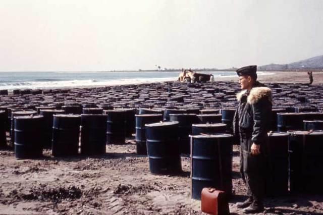 Playa de Quitapellejos llena de barriles con tierra contaminada para embarcar.