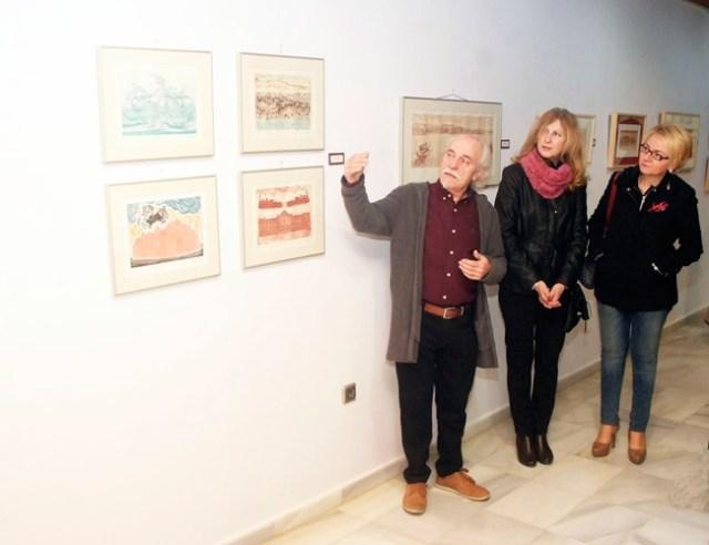 Antonio Egea habla sobre sus cuadros con Maria Dolores Ortega y Eloísa Cabrera.