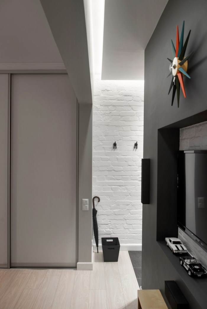 Simple-Sophistication-Concept-Involvement-in-Apartment-Entrance-and-Lounge-Area-with-Built-in-TV-Stand-and-Open-Sunburst-Wall-Clock-936x1402