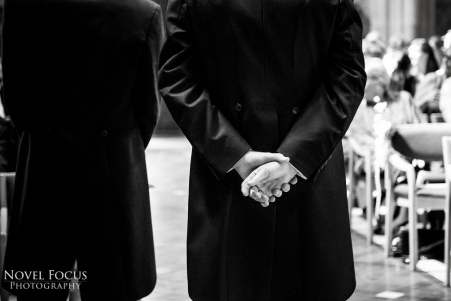 groom holding hands behind back at wedding ceremony