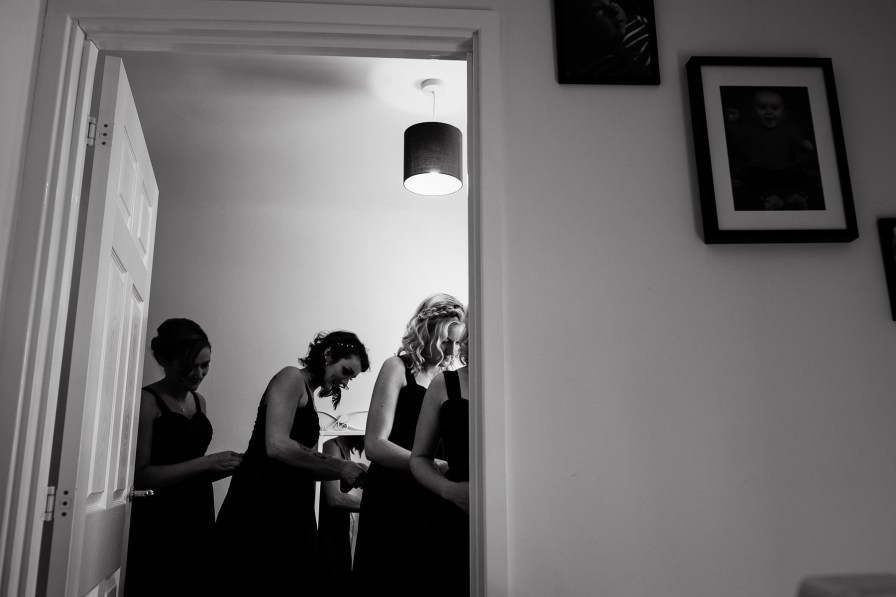 dress backs being done up in bridal preparation