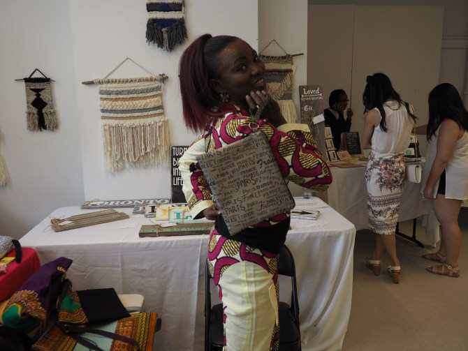 Martha, one of the vendors, models a bag she made. Martha is also a graduate of the Sew It program.