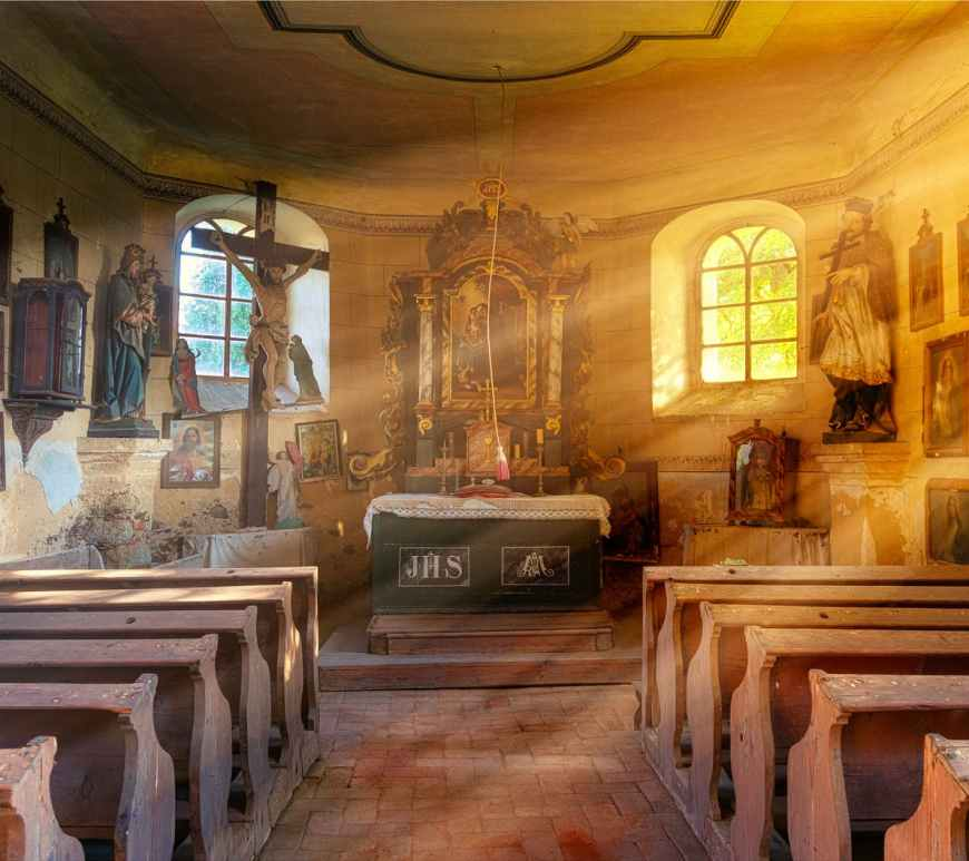 interior of old catholic church with bright rays of sun