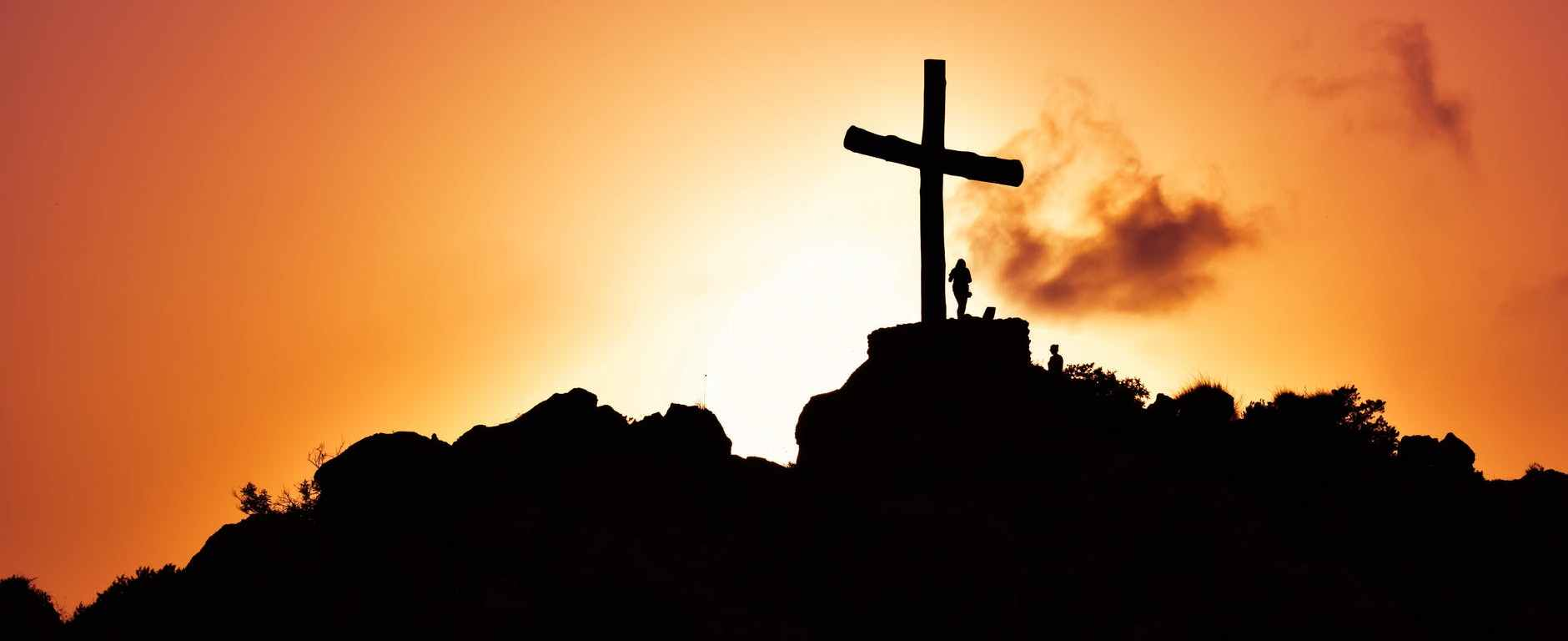 human standing beside crucifix statue on mountain