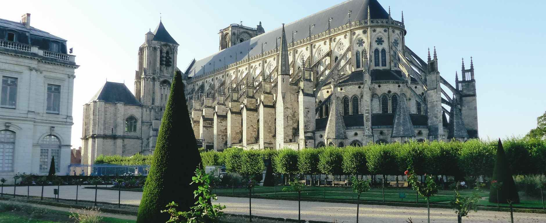 old catholic gothic cathedral among green plants of park