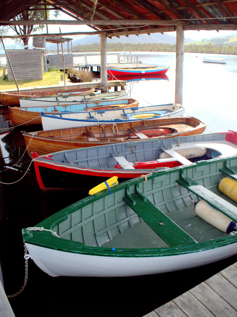 Colourful display of hand-built boats moored at the Wooden Boat Centre on the Huon River at Franklin