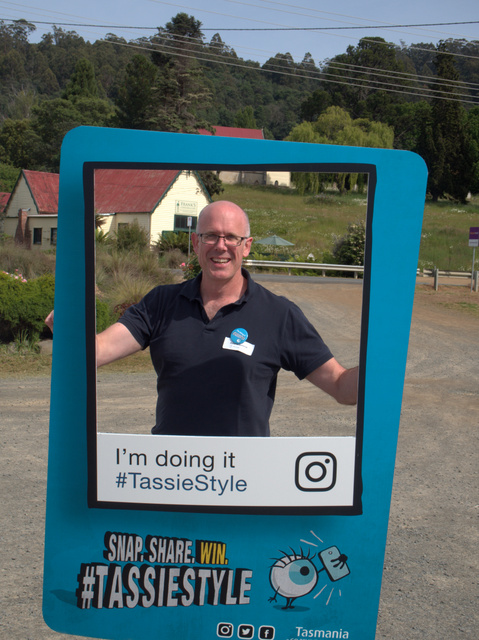Tourism Tasmania's Pete Kilpatrick poses with a sign promoting their latest advocacy campaign, #tassiestyle