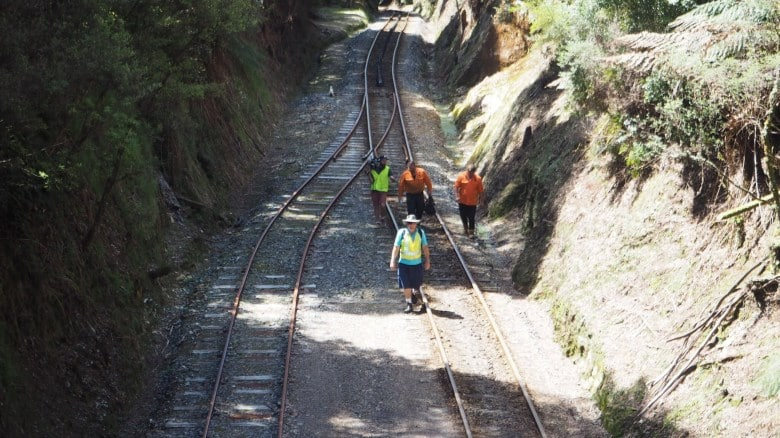 The crew in high-vis vests walks back up the line after filming the train's arrival at Rinadeena Station