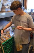 Eighth-grade student Wesley Sheller bags potatoes
