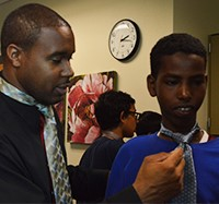 Jermale Eddie, employment and education specialist for Grand Rapids Urban League. helps Crestwood Middle School student Nur Nur tie a tie