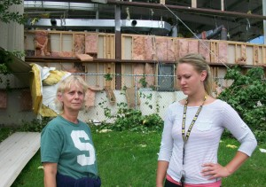 "Vicky Devine, left, has worked at the Well Mannered Dog Center for three years. ""I could cry. I was doing okay until I got here and saw it,"" she says of the building's destruction behind her. The center was boarding over 60 dogs over the holiday weekend. All dogs were found safe."