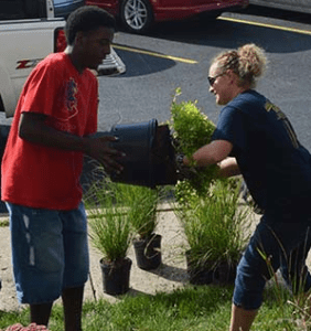 Arnell Scott, left, helps Katie Hoffman free a plant from its pot