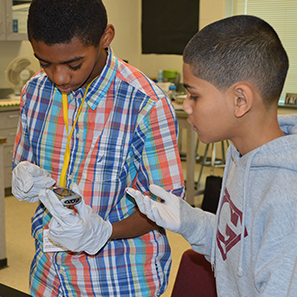 Sixth-graders Adonis Hughes and Mayson Clark learn how glucose testing works at Crestwood Middle School's career fair