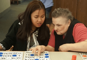 Kelloggsville High School senior Thu Nguyen plays bingo with a resident