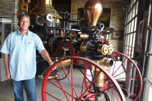 "Engine House Board President Jeff Blum stands next to the 1976 Silsby Steamer which will be part of this year's ""DreamWheels"" production."